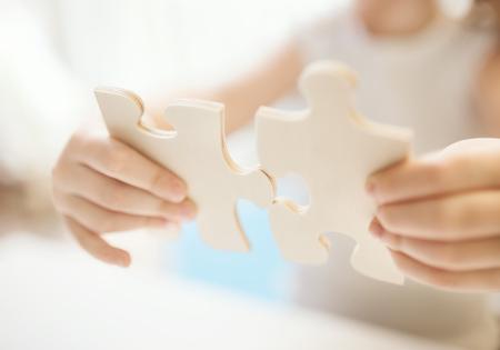 fille Enfant tenant deux grandes pièces de puzzle en bois. Hands connexion puzzle. Close up photo avec une petite DOF. L'éducation et l'apprentissage notion