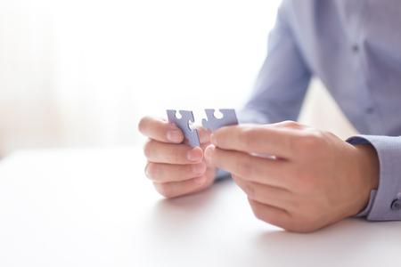 Geschäftsmann Hände Verbinden Puzzle. Business-Lösungen, Erfolg und Strategie, Lernkonzept. Close up Foto mit kleinen DOF. Standard-Bild