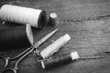scissors: Sewing accessories: bobbins of thread, scissors, needle, thimble on wooden table. Black and white photo. Tailoring and sewing concept