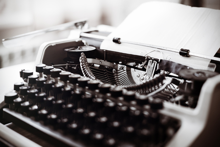 used: Old typewriter on wooden table. Vintage style tinted photo