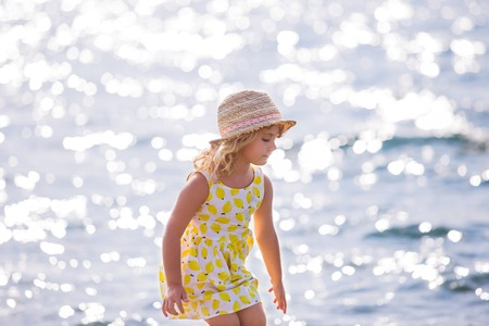 little girl dress: Cute little girl in yellow dress and straw hat standing barefoot on the waves along the beach on a summer sunny day Stock Photo