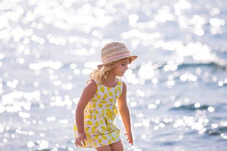 petite fille avec robe: Cute petite fille en robe jaune et chapeau de paille debout pieds nus sur les vagues le long de la plage sur une journée ensoleillée d'été