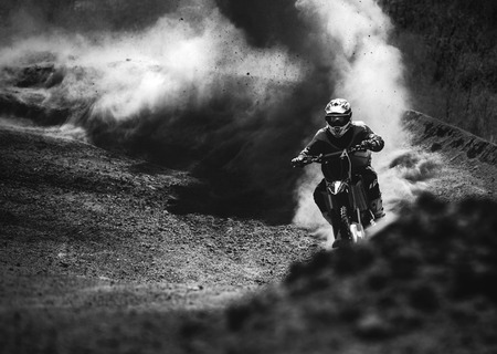 stunts: Motocross racer accelerating in dust track, Black and white, high contrast photo