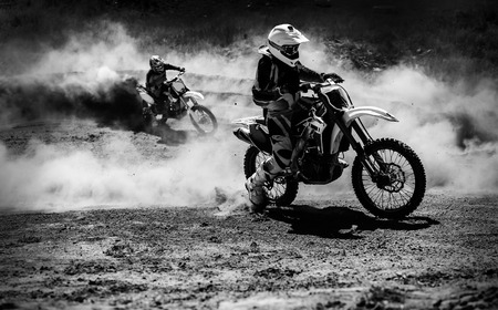 championships: Motocross racer accelerating in dust track, Black and white, high contrast photo