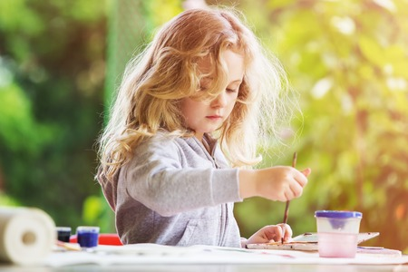 draw: Portrait of little blonde girl painting, summer outdoor