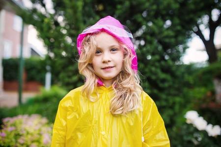 Outdoor photo of little blonde girl in yellow raincoat.
