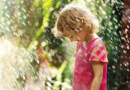 Photo of happy little girl standing under summer rain.
