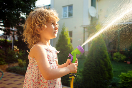 hosepipe: Little girl watering the grass in the garden.