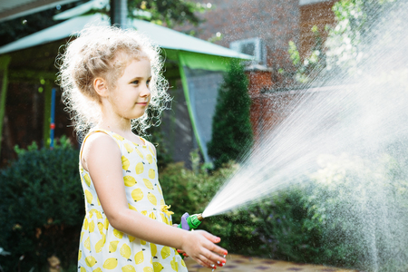 drench: Little girl watering the grass in the garden.