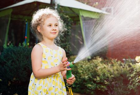 moisten: Little girl watering the grass in the garden.