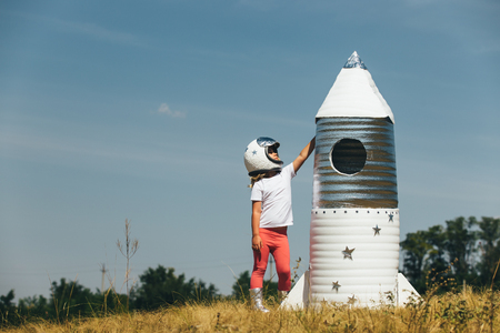 child rocket: Happy child girl dressed in an astronaut costume playing with hand made rocket. Summer outdoor.