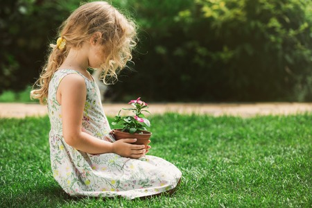 plant in pot: Little blonde girl holding young flower plant in hands on green background.