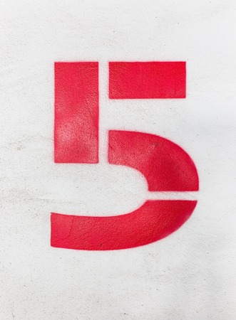 numerology: Red number 5 on cement texture, close up photo. Stock Photo