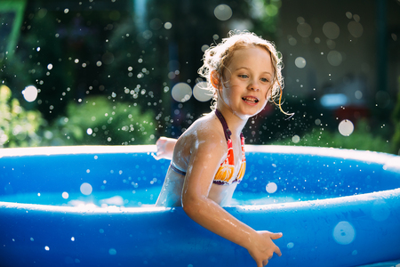 traje de baño: Retrato de niña linda en azul grande piscina inflable al aire libre.