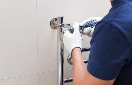 radiated: Plumber fixing chrome heated towel rail in bathroom.-