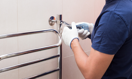 Plumber fixing heated towel rail in bathroom.-