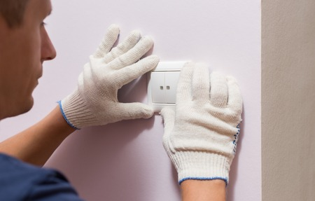 switch: Electrician installing light switch, close up photo.