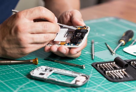 Man repairing broken smartphone, close up photo. Banco de Imagens - 62186378
