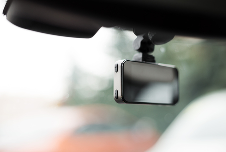 Car video recorder installed on front window, close up photo.