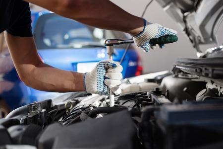Mechanik pracujący w warsztacie napraw auto. Utrzymanie samochodu. Zdjęcie Seryjne
