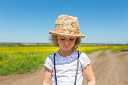 chapeau de paille: Petite fille dans le chapeau de paille à pied à travers le champ, en plein air d'été.