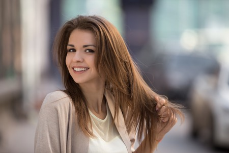 Portrait of beauty woman with perfect smile walking on the street and looking at camera.