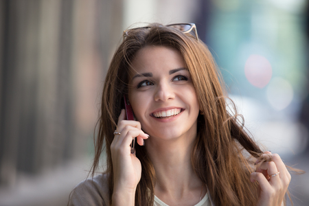 beautiful background: Happy young woman talking on mobile phone at city street lifestyle portrait Stock Photo