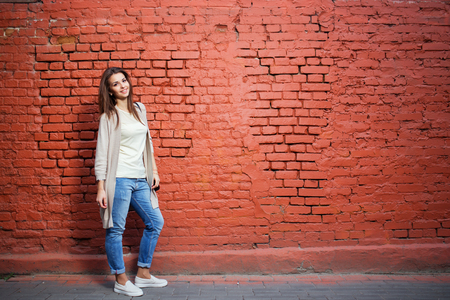 casual woman: Young beautiful happy woman in casual cloths against red brick wall