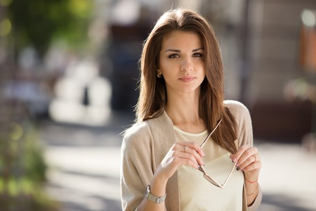 Portrait of beauty woman with perfect smile standing on the street and looking at camera.