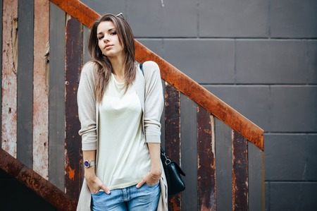 casual woman: Young beautiful happy woman in casual cloths against wall.