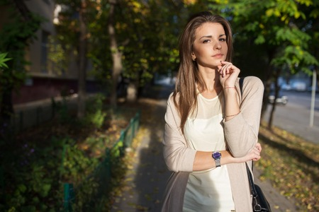 Portrait of beauty woman with perfect smile walking on the street and looking at camera. Sunset light