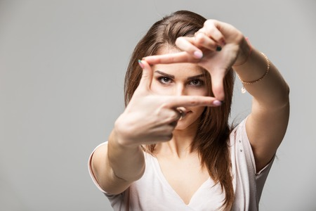 Closeup of young beautiful brunette woman making frame with her fingers, over gray background. Stock Photo