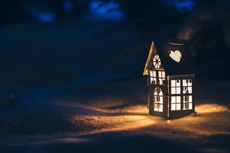 lit candle: Lantern house with burning candle on snow in the evening.
