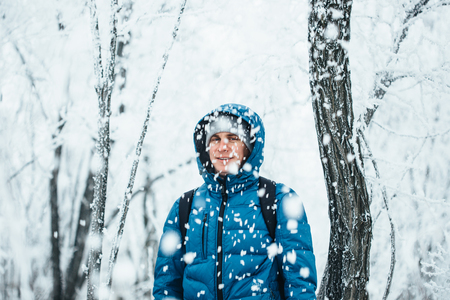 snowfalls: Young handsome man standing in snowfall on background of snowy forest.