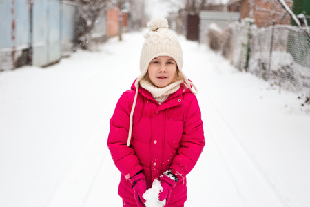 adorable child: Adorable child girl playing outdoor with snow