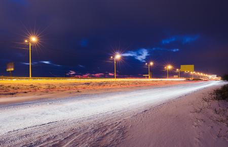 Route enneigée d'hiver la nuit brillant avec des lampes Banque d'images