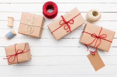 Eigengemaakte verpakte rustieke pakpapierpakketten op witte houten oppervlakte Stockfoto