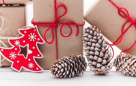 Homemade wrapped rustic brown paper packages with various natural things on white wooden surface
