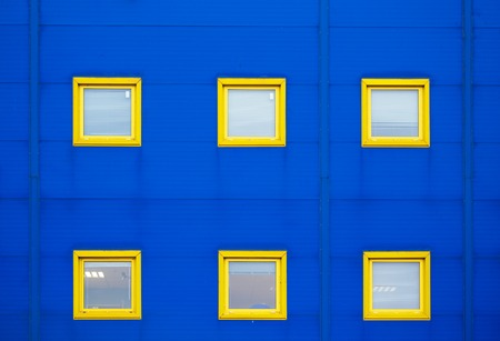 industry architecture: Facade of a modern blue warehouse and six yellow windows