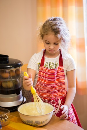 domestic life: Little blonde girl kneading dough in kitchen