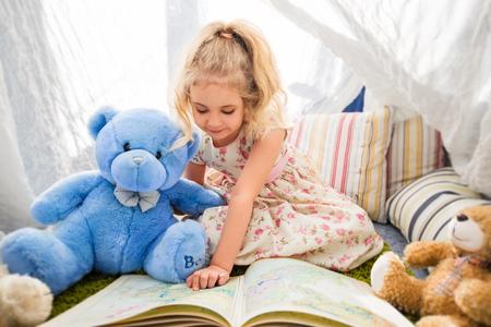 Kleines blondes Mädchen Kind in ihrem Zimmer zu Hause spielt mit Teddybären
