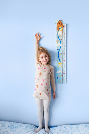 Little blonde girl measuring height against wall in room Foto de archivo
