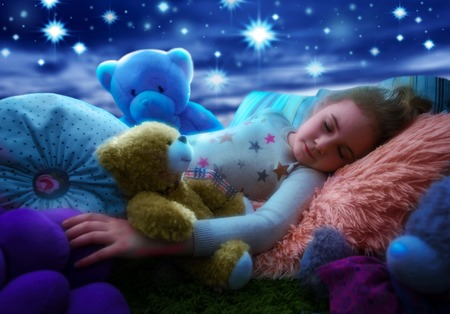Little girl sleeping with teddy bear in bed, dreaming the starry sky at bedtime night 免版税图像