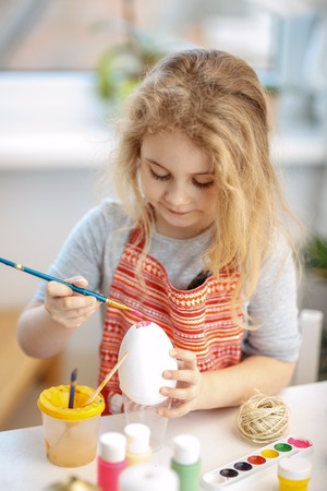 pascuas navideÑas: Little blonde girl coloring eggs for Easter holiday at home