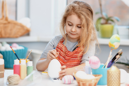 Little blonde girl coloring eggs for Easter holiday at home