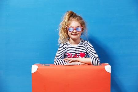 有桃红色葡萄酒手提箱的孩子白肤金发的女孩准备好暑假。旅行和冒险概念