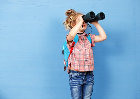 discovery: Happy child girl playing with binoculars. explore and adventure concept