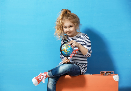 Child blonde girl with pink vintage suitcase study the globe. Tr