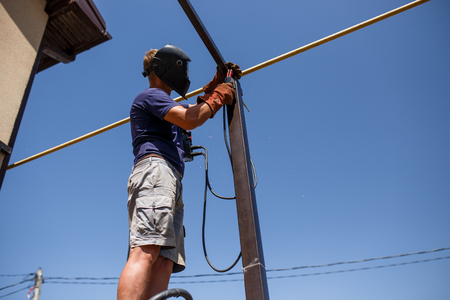 Man welding metal construction at his backyard. Фото со стока - 83472975