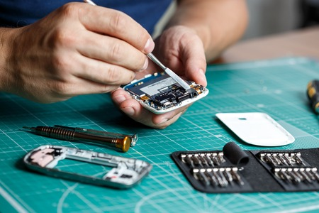 Electronics repair service. Technician disassembling smartphone for inspecting. Banco de Imagens - 83759770